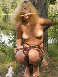 nude-blonde-with-tanlined-tits-and-bald-pussy-gets-tied-to-a-big-tree-and-tortured