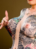 busty-transsexual-brunette-strips-to-show-her-tattooed-torso-and-to-give-a-close-up-of-her-dick