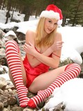 blonde-cutie-strips-out-of-her-red-and-white-christmas-uniform-in-the-winter-forest