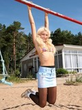 blonde-girl-in-black-pantyhose-and-blue-skirt-does-exercises-on-the-play-ground