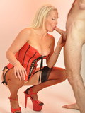 Blonde in red corset and short black skirt shows her shaved cunt and gives mouthjob