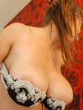 Brown haired lady in lingerie takes off her bra to show her massive natural tits