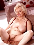 playful-blonde-haired-granny-in-red-lingerie-smiles-and-shows-her-tits-and-cunt