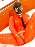 asian-tranny-in-black-gas-mask-and-orange-latex-suit-shows-her-cock-and-anus