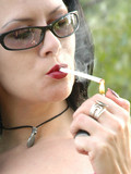 sexy-brunette-in-black-bra-and-pink-top-smoking-a-cigarrete-in-the-park