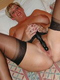 short-haired-mature-woman-in-black-nylons-playing-with-her-favorite-toys