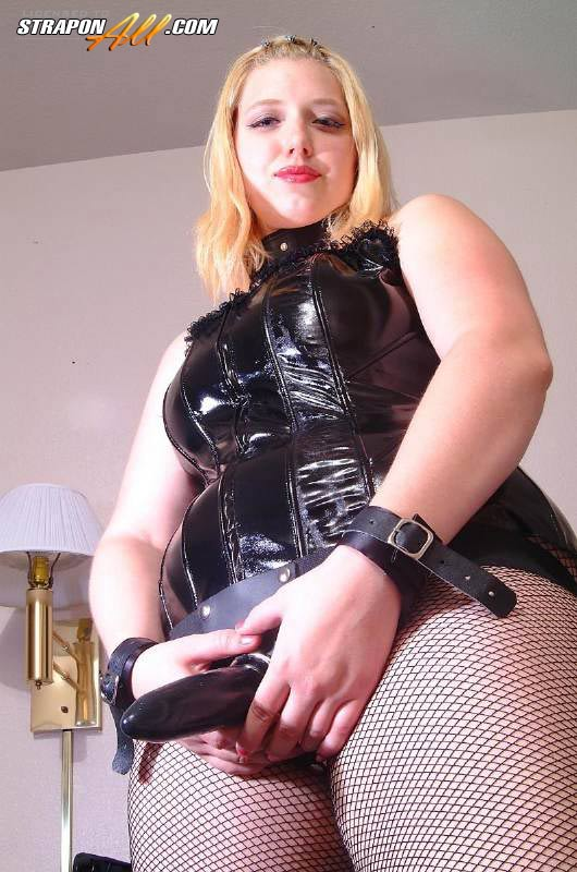 bbw strapon latex - Blonde mistress in fishnet pantyhose and latex corset shows her new strapon