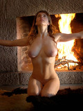 Naked big breasted temptress shows off her gorgeous body by the fireplace