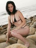 pale-skinned-brunette-milf-with-nice-body-poses-in-black-string-bikini-outdoors