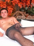 dark-haired-guy-in-black-pantyhose-masturbates-on-a-king-size-white-bed