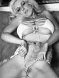 Attractive retro blonde with enormously big tits opens her legs and shows her slit