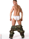 Guy with short fair hair poses in military style clothes and gets totally nude