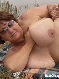topless-mom-touches-her-monstrous-breasts-while-lounging-on-the-ground-by-the-lake