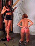 naked-obedient-redhead-girl-gets-whipped-by-long-legged-brunette-domina